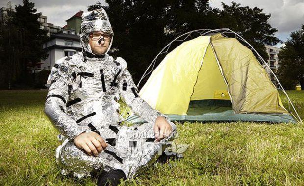 Мужчина в алюминиевой фольге сидит у палатки, фото