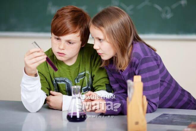 Школьники на уроке изучают пробирку с химической реакцией, фото