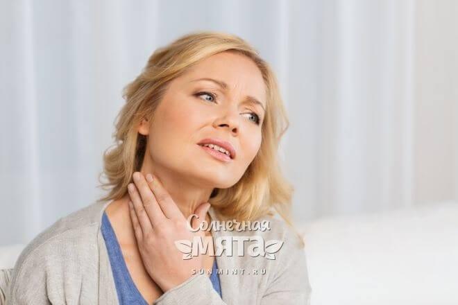 Обеспокоенная женщина проверяет свою щитовидку, фото