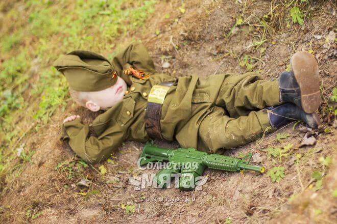 Маленький мальчик в костюме солдата спит на земле, фото