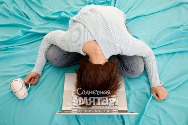 Уставшая девушка лежит на ноутбуке, фото