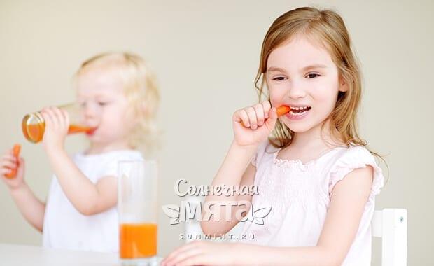 Две маленьких девочки едят морковь и пьют морковный сок, фото