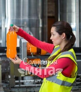 Женщина проверяет фабричный сок с витамином C на конвейере, фото