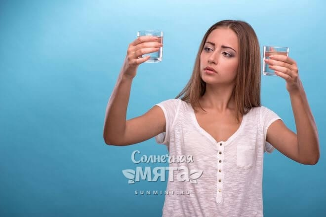 Девушка внимательно смотрит на стакан с водой, фото
