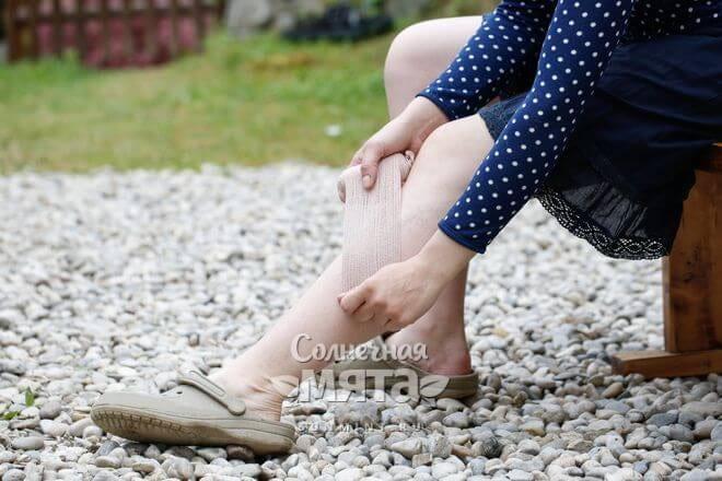 Пожилая женщина бинтует себе ногу, фото