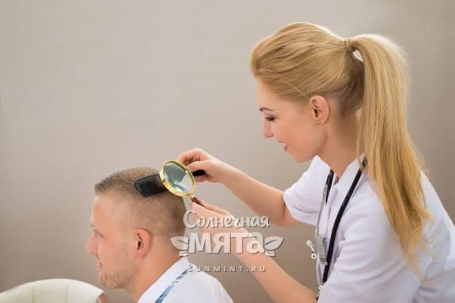 Доктор осматривает кожу головы пациента, фото