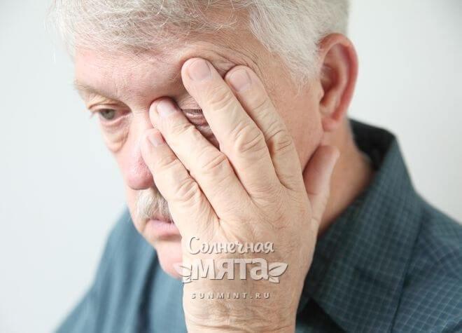 Пожилой мужчина страдает от болезни глаз, фото