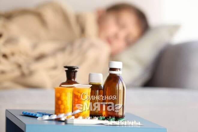 Лекарства на тумбочке рядом с больным мальчиком, фото