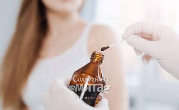 Доктор держит в руках флакончик с йодом, фото