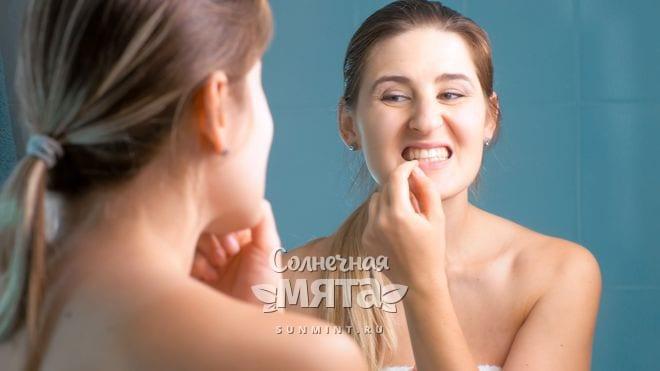 Девушка проверяет свои зубы на кровоточивость при дефиците витамина P, фото