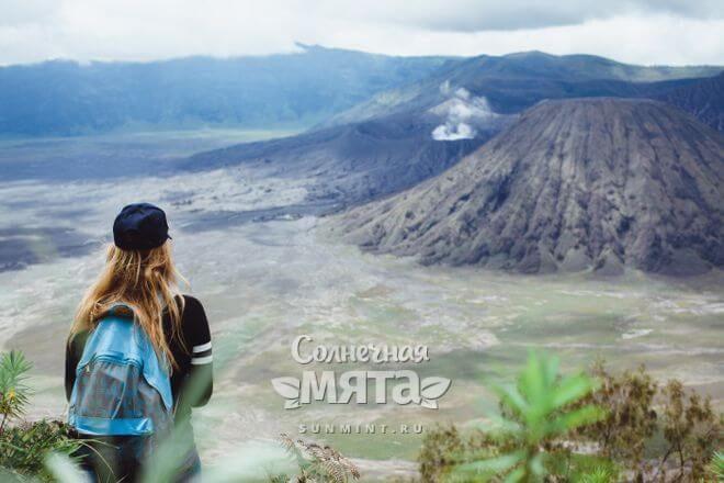 Девушка-турист смотрит на вулкан, фото