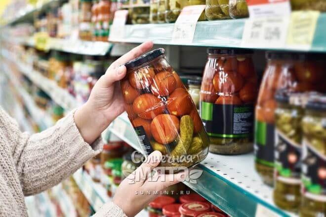 Женщина выбирает банку с соленьями в магазине, фото