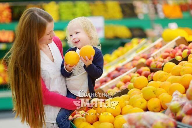 Мама с дочкой покупают апельсины с витамином С, фото