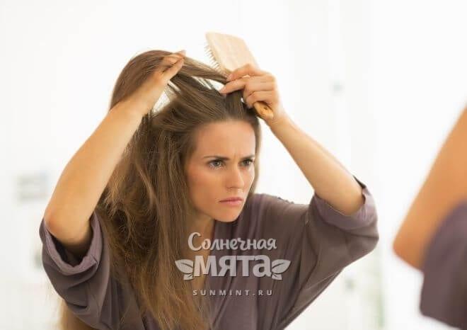 Обеспокоенная девушка расчесывает волосы перед зеркалом