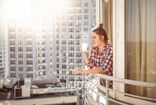 Девушка пьет кофе на балконе многоэтажки, фото