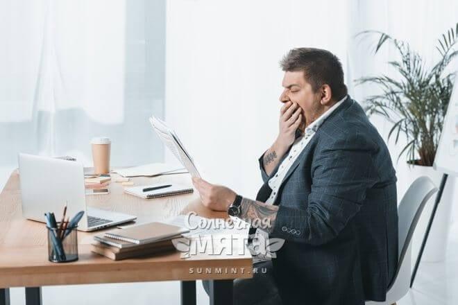 Полный мужчина зевает за прочтением газеты, фото