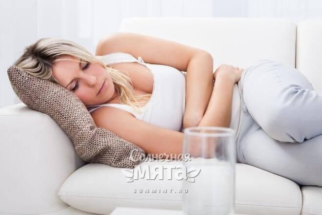 Девушка лежит на диване с больным животом, фото