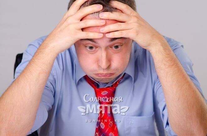 Раздраженный и уставший мужчина на работе, фото