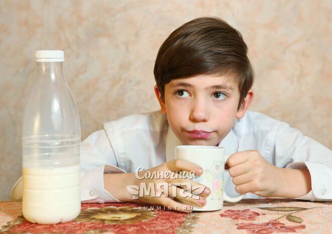 Сомневающийся мальчик пьет молоко, фото