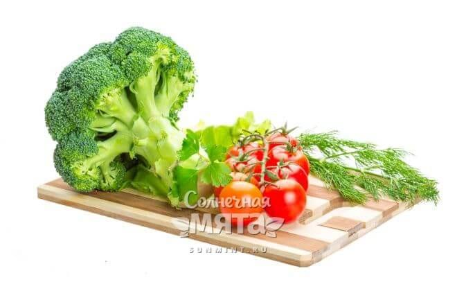 Брокколи и помидоры на разделочной доске, фото