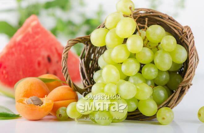 Корзинка с виноградом, персиками и арбузом на столе, фото
