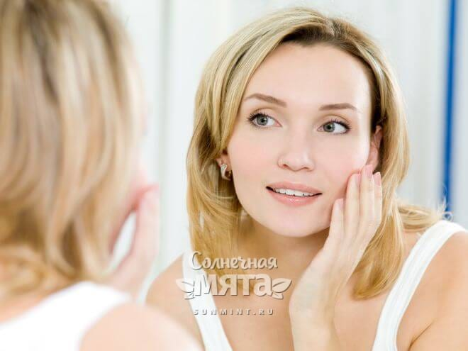 Женщина смотрит на свое лицо в зеркале, фото
