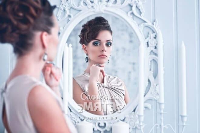 Красивая женщина с украшениями из серебра смотрит на себя в зеркало, фото