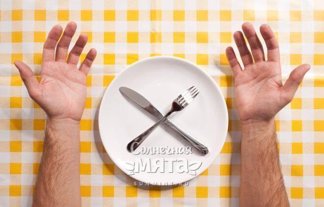 Руки мужчины по обе стороны от пустой тарелки, фото
