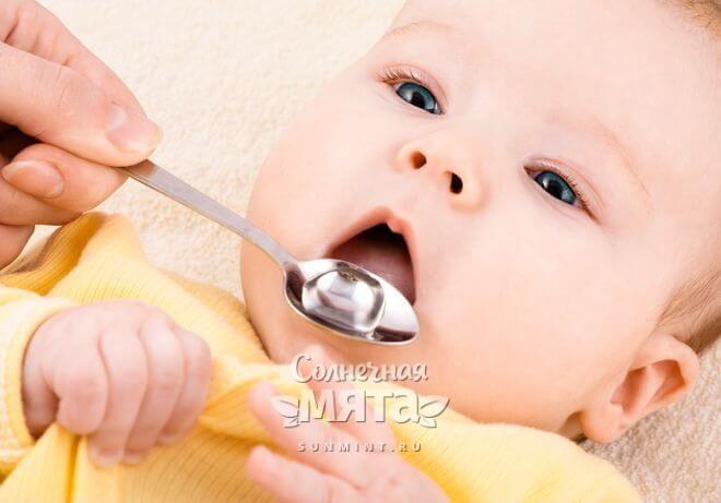 Мама дает младенцу сироп с серебряной ложечки, фото