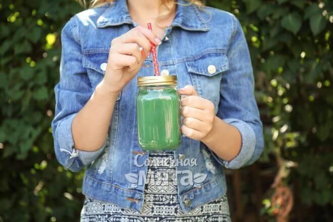 Девушка держит в руках зеленый коктейль со спирулиной, фото