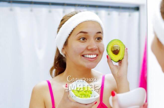 Девушка стоит перед зеркалом с авокадо, содержащим витамин B5, фото