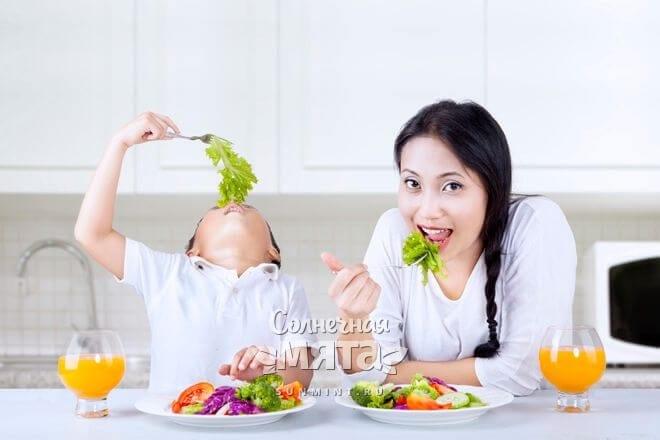 Мама с сыном едят свежий салат с витамином Е, фото