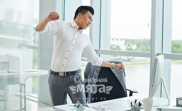Работник офиса потягивается на рабочем месте, фото