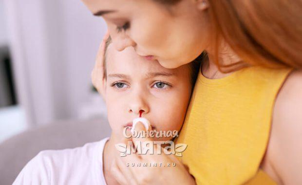 Мама вытирает кровь из носа своей дочери, фото