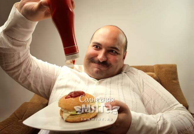 Толстый обжора поливает гамбургер кетчупом, фото