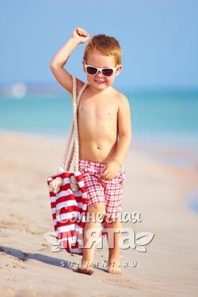 Мальчик с сумкой гуляет по пляжу, фото
