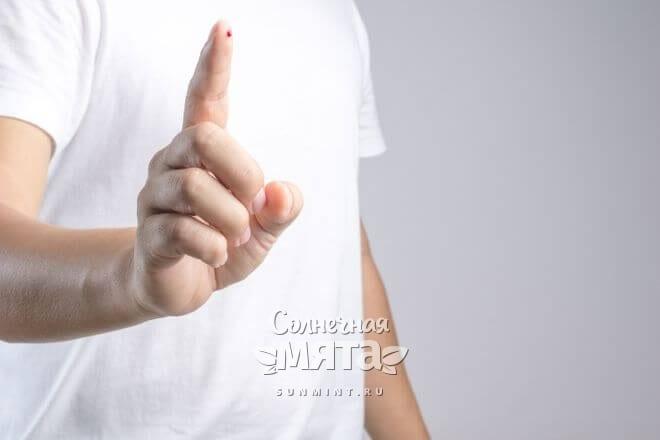 Мужчина показывает каплю крови на своем пальце, фото