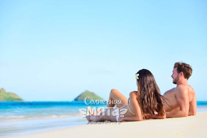 Молодая пара загорает на пляже у океана, фото