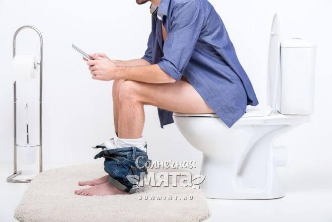 Мужчина сидит на унитазе с планшетом в руках, фото