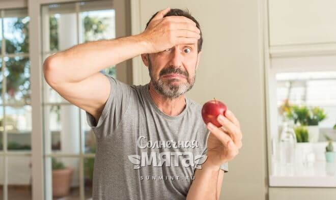 Взрослый мужчина удивляется новой диете, держа в руках яблоко, фото