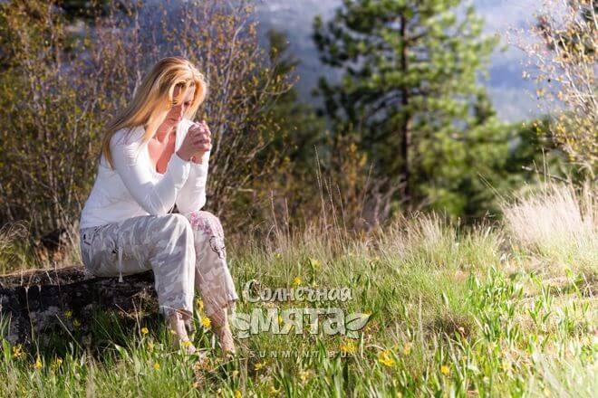 Женщина размышляет, сидя на природе, фото