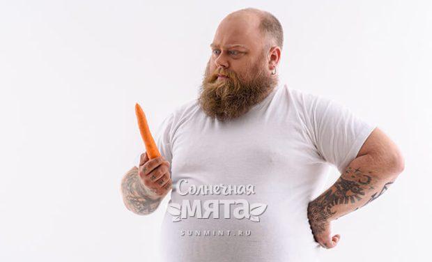 Полный мужчина смотрит на морковку, фото