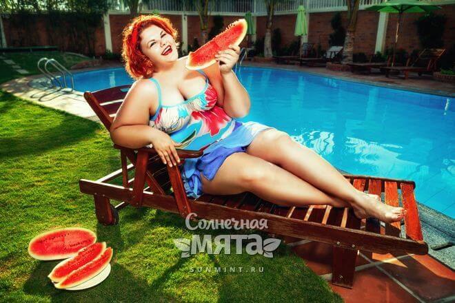 Полная женщина ест арбуз, лежа у бассейна, фото
