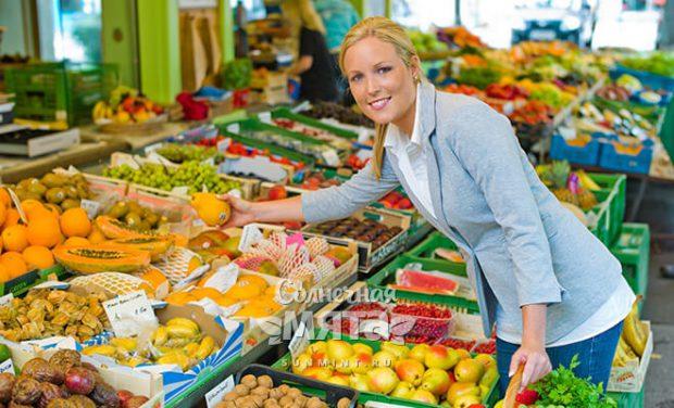 Женщина на рынке выбирает овощи, фото