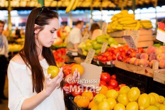 Задумчивая девушка на рынке выбирает фрукты, фото