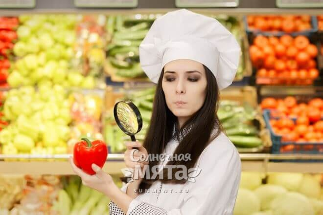 Женщина-повар с подозрением смотрит на перец через лупу, фото