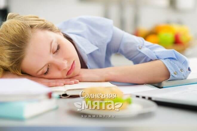 Уставшая девушка спит за столом перед гамбургером, фото