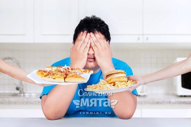 Мужчина не хочет смотреть на пиццу, гамбургер и картошку-фри, фото