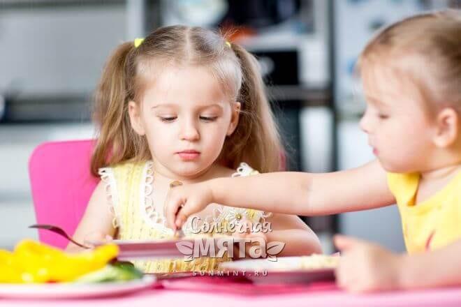 Девочка в детском садике смотрит в свою тарелку, фото
