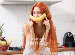 Девушка прикладывает к своему рту банан в форме улыбки, фото